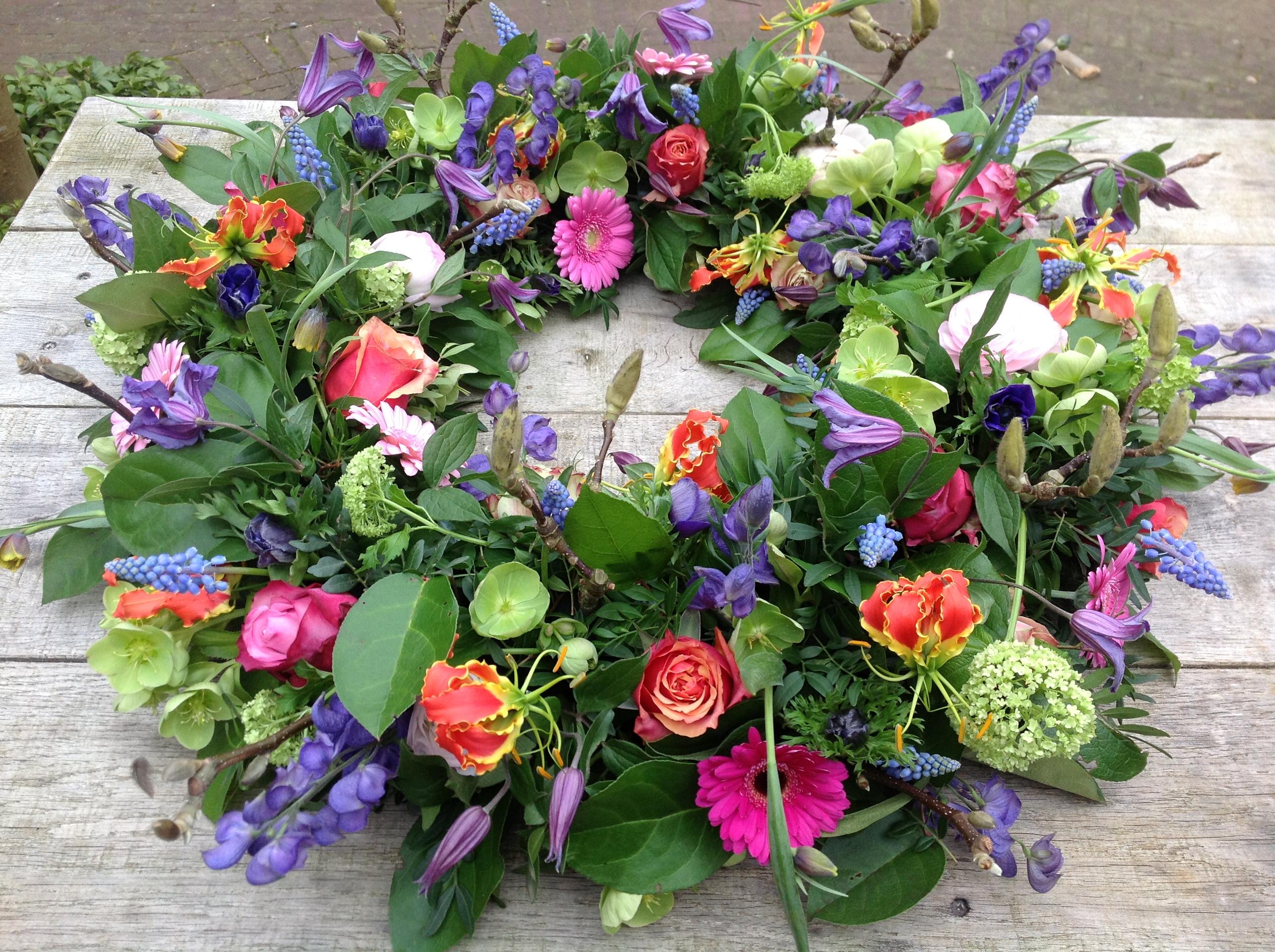 Rouwkrans gemaakt van gekleurde voorjaarsbloemen